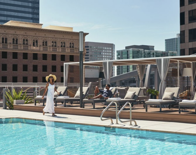 woman walking by pool with view of buildings