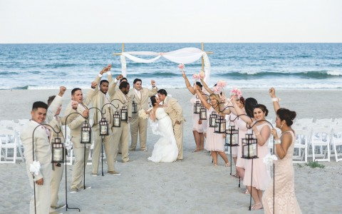 Bride and groom kissing in between bridesmaids and groomsmen on the beach