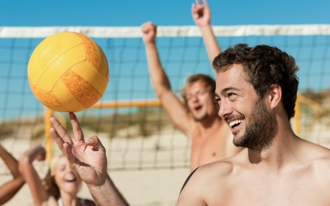 Man playing with volleyball with friends cheering in the back