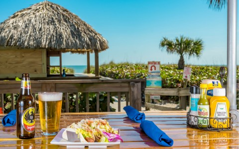 Wooden set with meal & beer overlooking tiki hut & ocean