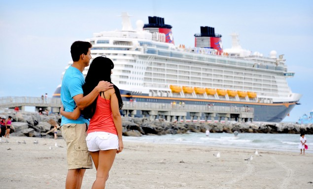 Couple standing by the ocean with cruise ship in water