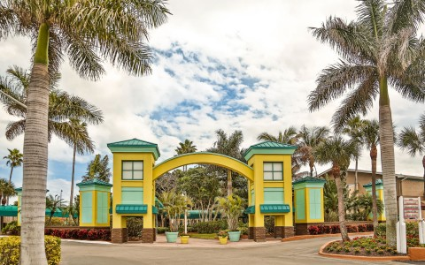 Hotel entrance with yellow & aqua arc surrounded by palm trees
