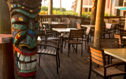 Outdoor dining area with tables chairs & decorative tiki pole