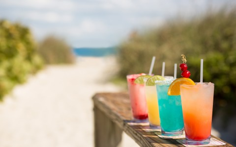 Colorful cocktails on wooden ledge by the beach