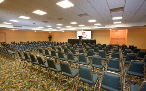Event space with projection screen and rows of chairs