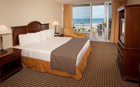 Room with king bed, wooden nightstands, dresser & balcony with ocean view