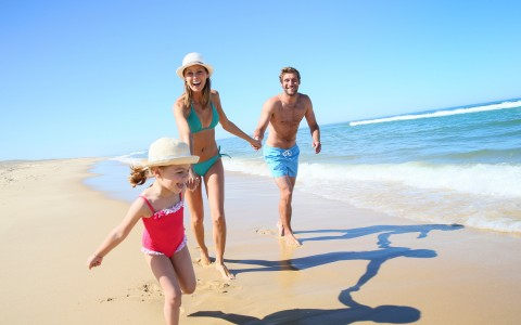 Couple with daughter running on the sand by the ocean water