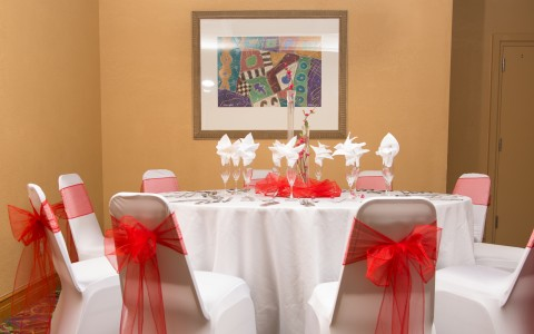 Table set for meal with white tablecloth & red decor accents