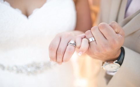 Close up of bride and groom hands wearing wedding bands