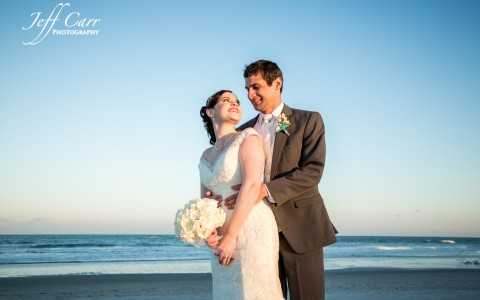 Groom hugging bride from behind on beach