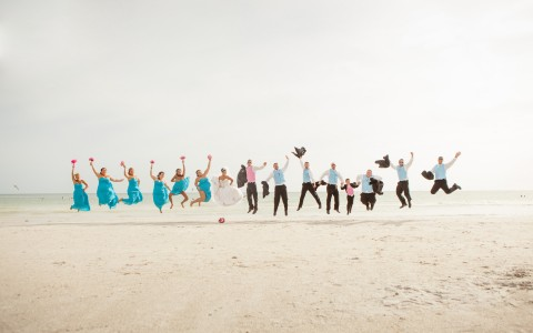 Wedding couple, bridesmaids & groomsmen jumping in the air on beach