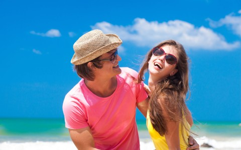 man and woman in bright colors laughing on the beach