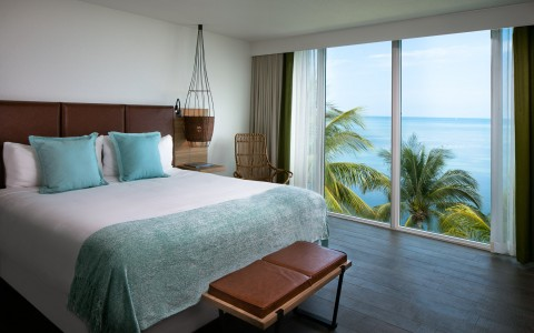 Suite bed with a large window and ocean view