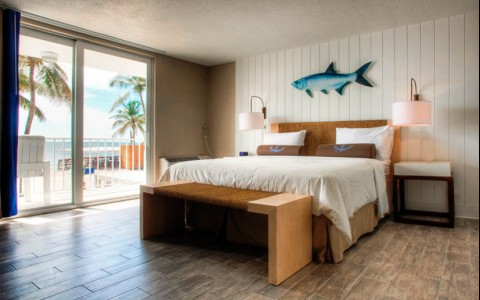 King bedroom with white comforter and fish hanging on the wall