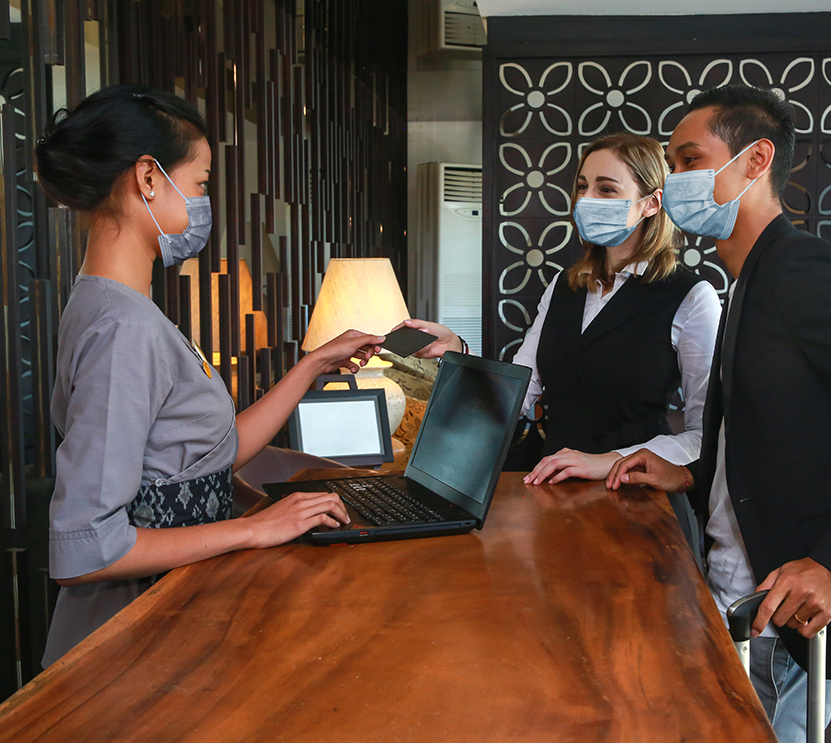 couple cheking into hotel with masks