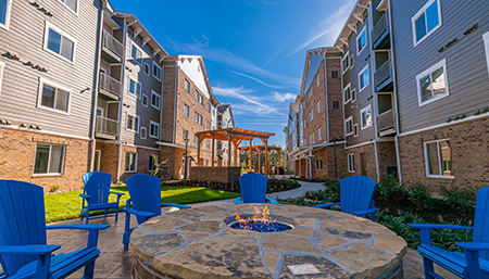 Exterior of hotel on a sunny day with firepit and blue lawn chairs