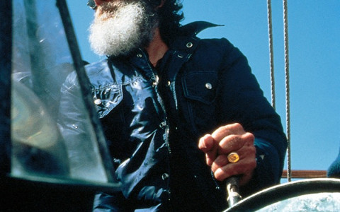 man with a beard and sunglasses steering a boat