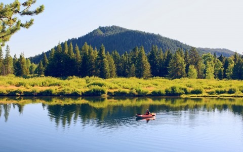 kayaker in water by mountain and trees