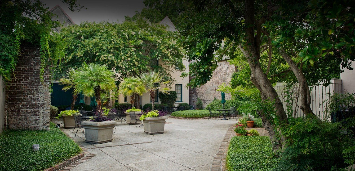 Lush garden courtyard with entry way to hotel