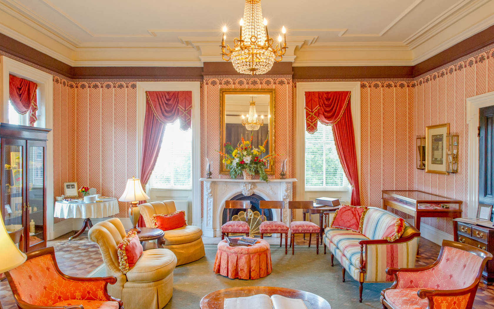 Elegant living space with peach padded chairs, yellow sofa, red curtains & crystal chandelier