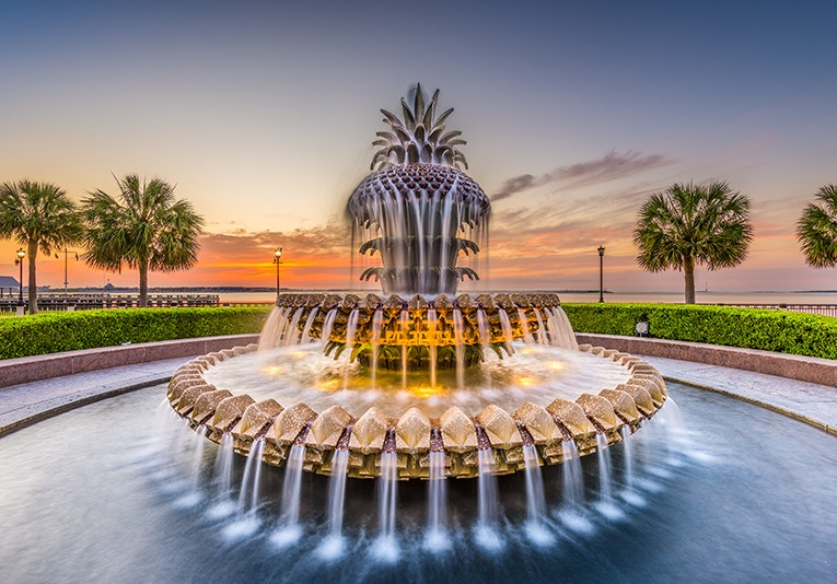 Pineapple fountain at sunset with palm trees