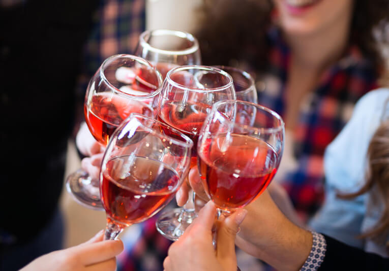 Close up of group of people toasting with red wine