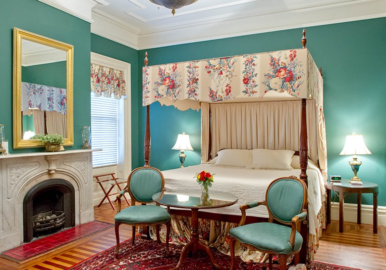 Canopy bed with antique furnishings in a green room