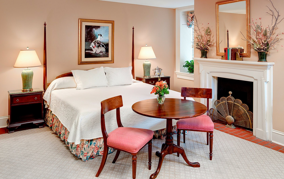 Room with king bed, wooden bed frame, seating area with wooden table, fireplace & nightstands