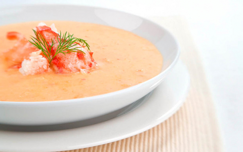 Light orange soup with herbs in the center