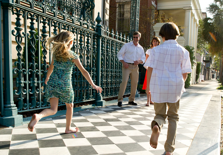 Two young kids running toward adults in front of hotel