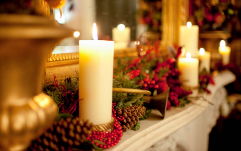 Lit up candles with holly berries & pine cones on top of fireplace