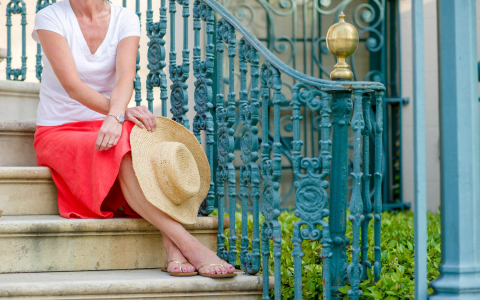 Woman sitting on stairs with turquoise railing