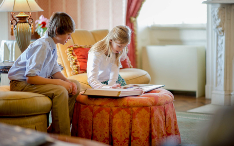 Two kids seated on bright colored furniture looking at photo album
