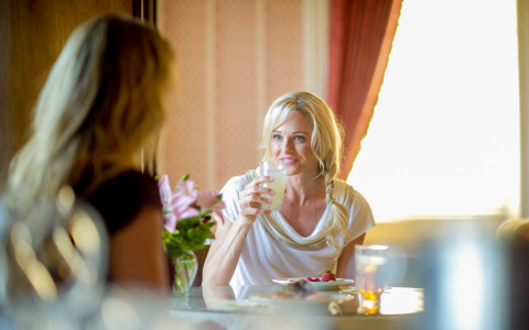 Two women seated at indoor table enjoying breakfast