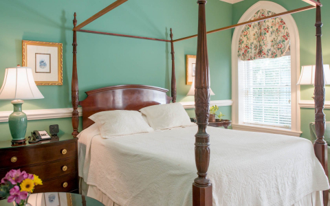 Room with king bed, wooden bed frame, nightstands & mint green wall