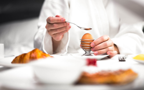 Chef placing hard boiled egg in wire holder