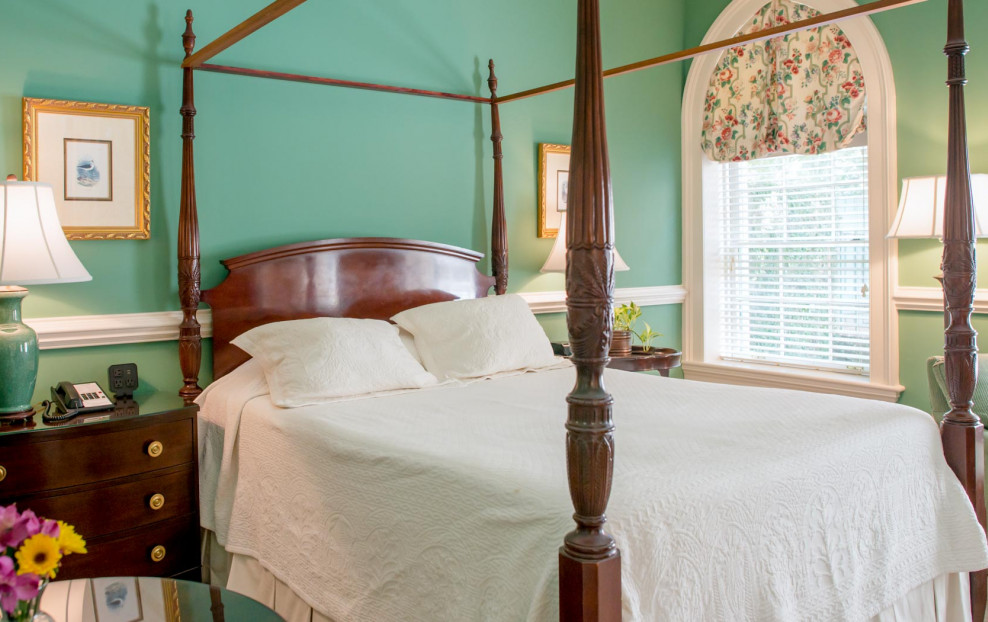 green walled bedroom with four poster bed and white comforter