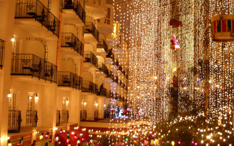 String christmas lights hung from buildings along street