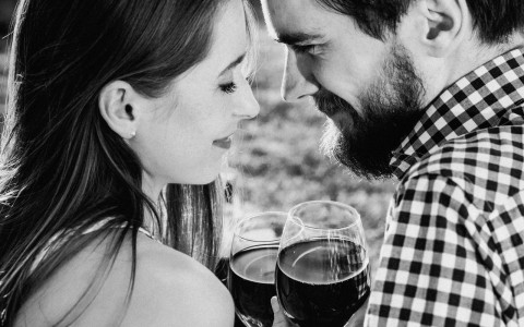 Black and white image of couple with glasses of wine