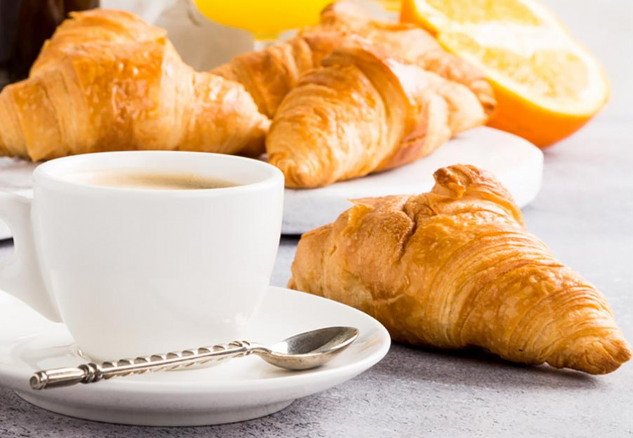 Breakfast tray with two croissants, orange juice and french press coffee