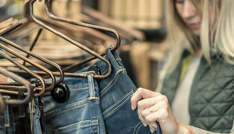 Woman looking at jeans hung on rack