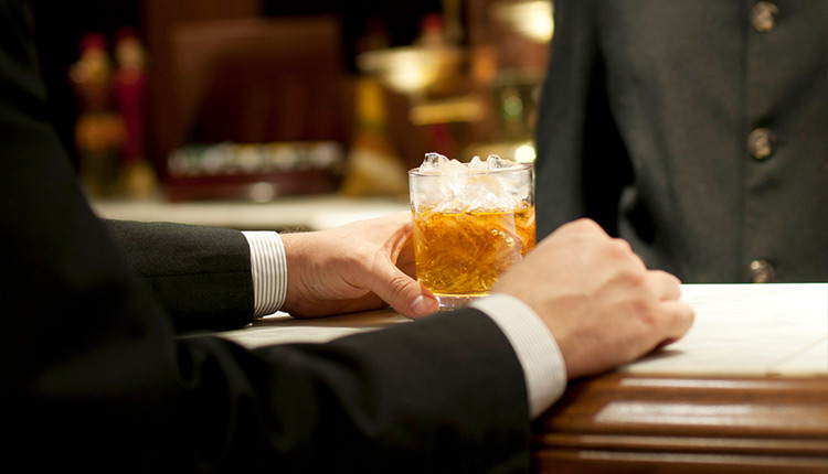 Close up of man in suit grabbing glass of bourbon