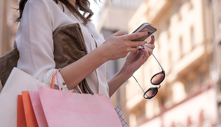 Close up of woman using cellphone & holding shopping bags
