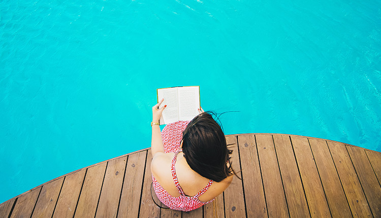 woman reading poolside