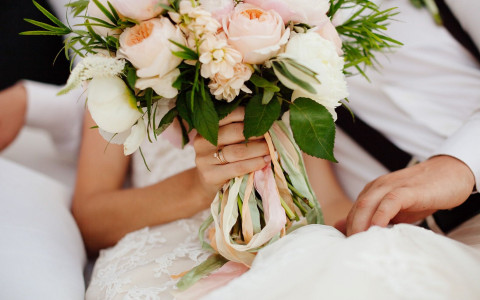 Close up of bride holding rose bouquet
