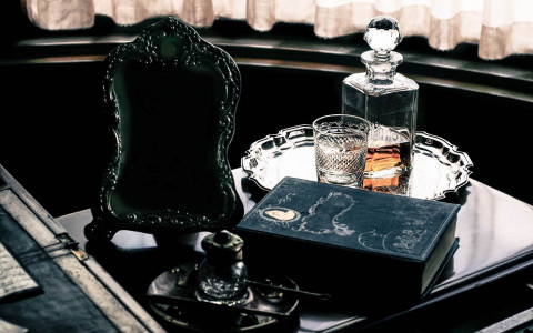 Tray with bottle and glass of bourbon next to antique mirror & book