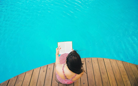 Overhead shot of woman reading magazine beside the pool