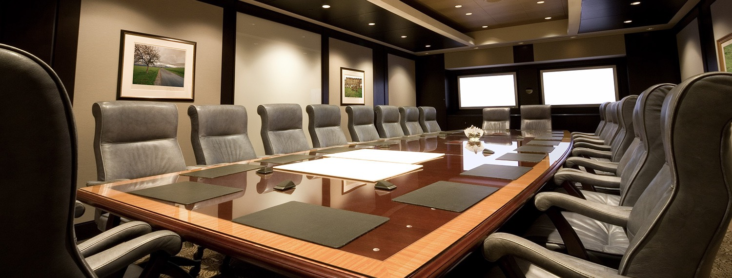 Long wooden meeting table with black cushioned chairs