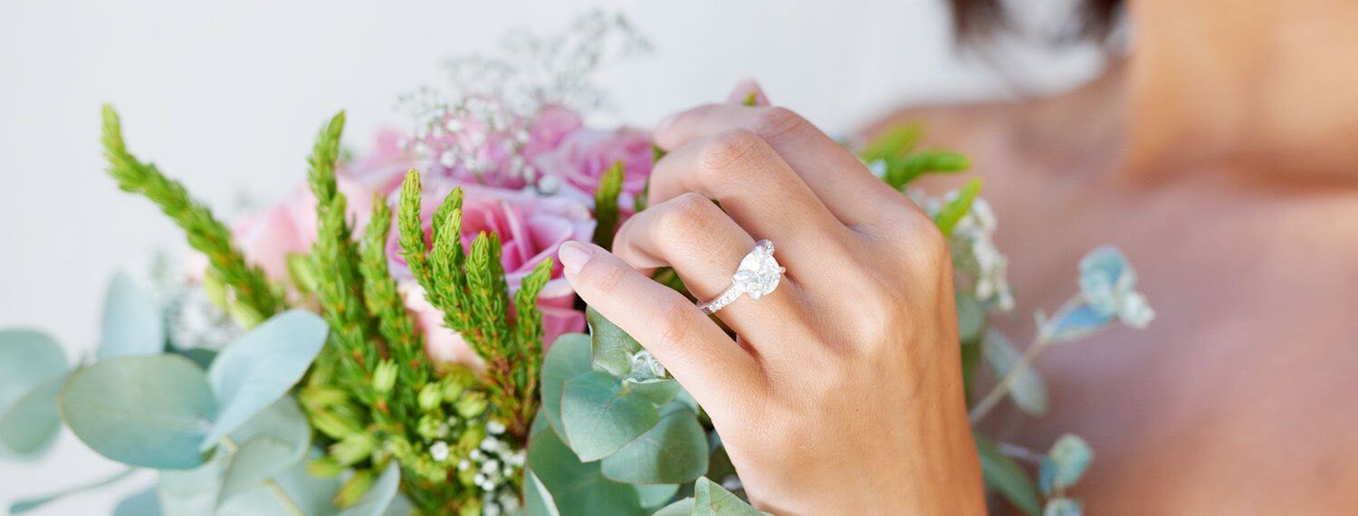 Close Up Shot of a bride holding a bouquet of flowers with her engagement ring on her left hand