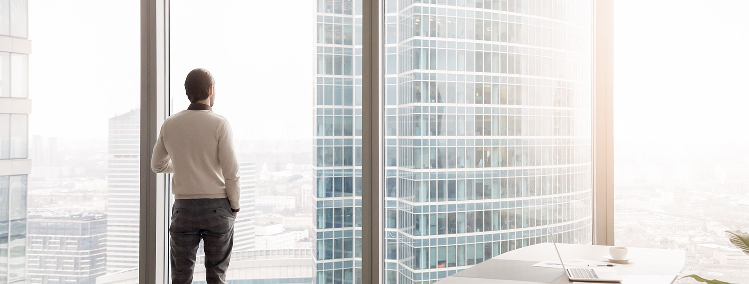 Man looking at city from meeting room large panel windows